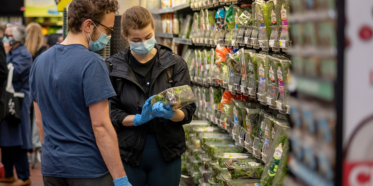 People wearing masks and gloves shop for groceries at a New York City supermarket on May 1. (Alexi Rosenfeld/Getty Images)