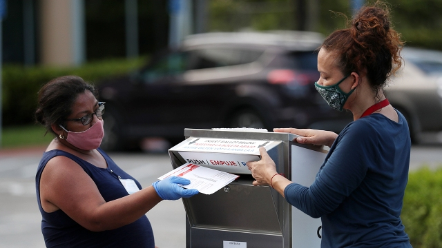 Poll workers deposit mail-in ballots on primary day on August 18, 2020, in Doral, Florida. (Joe Raedle/Getty Images)