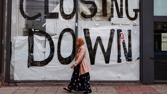 A woman walks past a closed shop in London on June 28. (Hollie Adams/Getty Images)