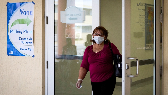 A woman wearing a protective mask and gloves leaves after voting in Florida's Democratic primary election at Miami-Dade Public Library Little Havana in Miami on March 17, 2020. (Eva Marie Uzcategui/AFP via Getty Images)