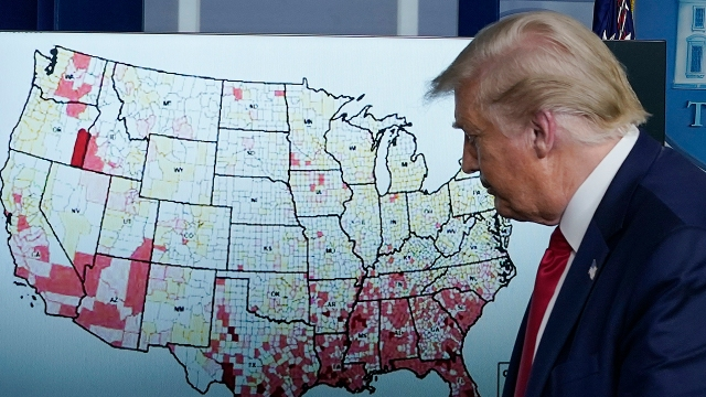 President Donald Trump in July walked by a map of U.S. coronavirus cases per 100,000 people. (Drew Angerer/Getty Images)