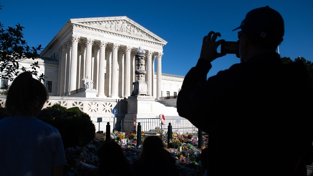 A visitor takes photos near a makeshift memorial for late U.S. Supreme Court Justice Ruth Bader Ginsburg at the U.S. Supreme Court on Sept. 21, 2020. (Saul Loeb/AFP via Getty Images)