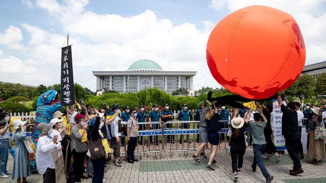 Climate activists hold a large red balloon representing the Earth on June 11, 2020, in Seoul, South Korea. (Chris Jung/NurPhoto via Getty Images)