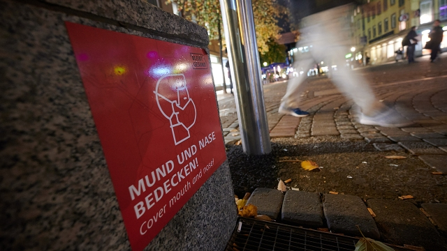 A sign in the old town area of Düsseldorf, Germany, calls on people to cover their nose and mouth. (Henning Kaiser/picture alliance via Getty Images)