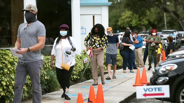 Voters wait in line, socially distanced from each other, to cast early ballots on Oct. 19, 2020, in Miami, Florida. (Joe Raedle/Getty Images)
