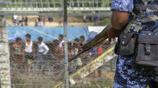 "Border guard police in Burma (Myanmar) patrol the fence in the ""no-man's land"" at the country's border with Bangladesh in August 2018. More than 14,500 Rohingya Muslims were reported to have fled to Bangladesh in 2018 to escape abuses, and at least 4,500 Rohingya were stuck in the border area. (Phyo Hein Kyaw/AFP via Getty Images)"