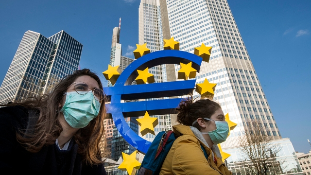 Students in masks pass the Euro sculpture in downtown Frankfurt, Germany, in March 2020. Restrictions had taken effect the week before to stem the spread of the coronavirus. (Thomas Lohnes/Getty Images)