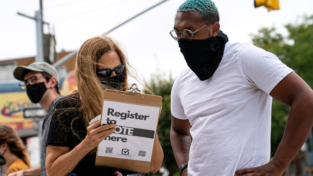 A volunteer with Brooklyn Voters Alliance registers a New York resident to vote in September. (Robert Nickelsberg/Getty Images)