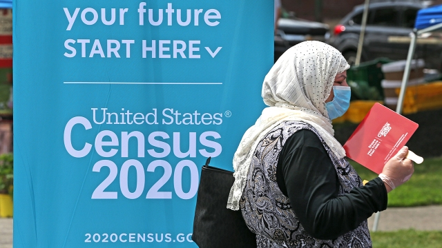 A woman waits at a Census 2020 booth at a farmers market in Everett, Massachusetts, in July. (David L. Ryan/The Boston Globe via Getty Images)