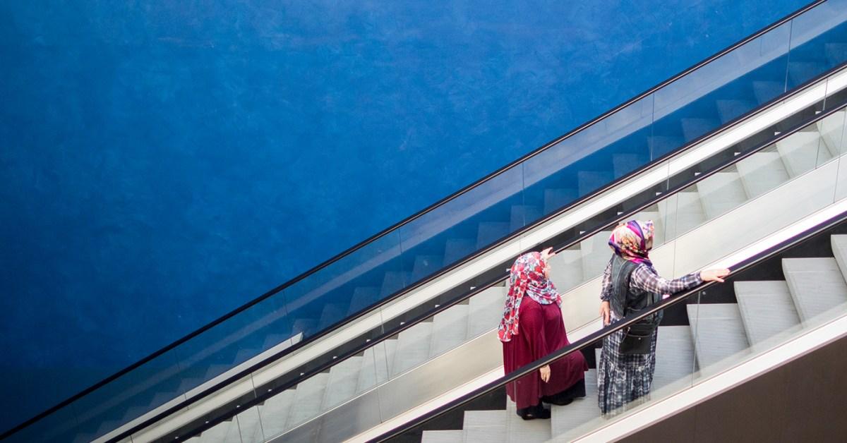 Two women wearing headscarves stand on an escalator in Essen, Germany, in 2018. (Rolf Vennenbernd/DPA/AFP via Getty Images)