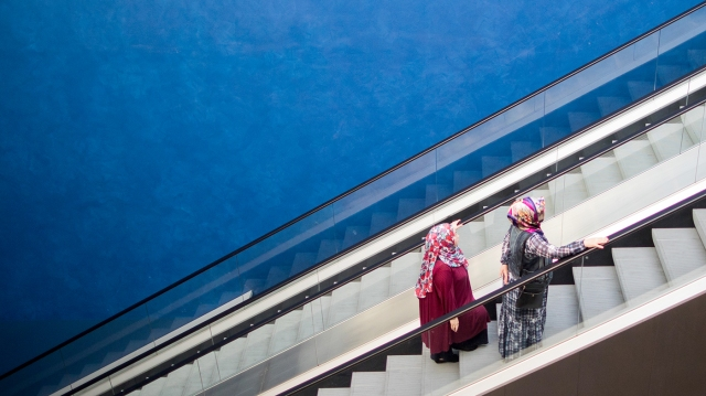 Two women wearing headscarves stand on an escalator in Essen, Germany, in 2018. (Rolf Vennenbernd/DPA/AFP via Getty Images)