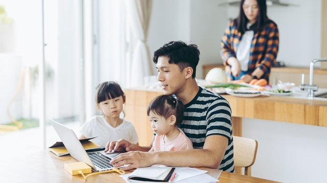 An adult works at a table with two young children watching, while another person in the household prepares food in a different part of the room. (Getty Images)
