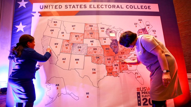 Two people fill in a map of the U.S. that is color-coded by Electoral College results. (BYAMBASUREN BYAMBA-OCHIR/AFP via Getty Images)