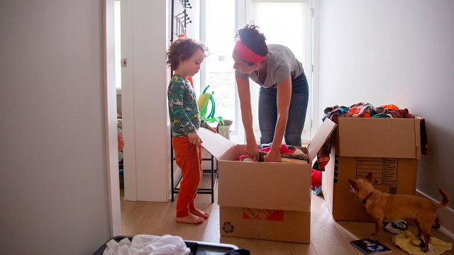 A young boy helps his mother unpack toys at their new home in El Cerrito, California, in September 2020. They had moved to be closer to family in part because of COVID-19. (Brittany Hosea-Small/AFP via Getty Images)
