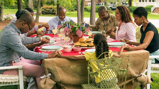 A multi-generation Black family prays at a picnic table. (Mark Edward Atkinson/Tracey Lee via Getty Images)