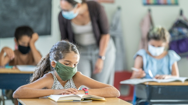 A young student wearing a mask sits in a classroom with peers and a teacher. (Getty Images)