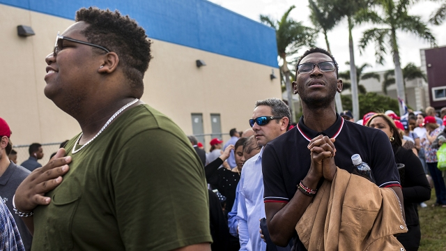 "Two men sing along with Christian music played over loudspeakers while waiting in line for an ""Evangelicals for Trump"" rally in Miami in January 2020. (Scott McIntyre/The Washington Post via Getty Images)"