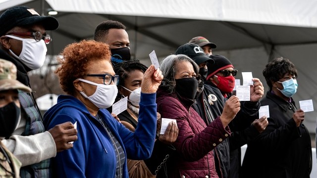 Coronavirus vaccine recipients show off their vaccination record cards in the parking lot of Six Flags in Bowie, Maryland, on Feb. 6, 2021. The state is using the lot as a mass vaccination site. (Sarah Silbiger/Getty Images)