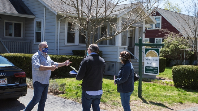 Rick Nazarro of Colonial Manor Realty talks with a pair of interested buyers waiting to enter a property on May 2, 2020, in Revere, Massachusetts, for an open house conducted under COVID-19 protocols. (Blake Nissen for The Boston Globe via Getty Images)
