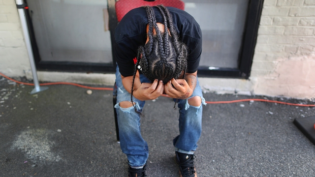 A person bows her head in her hands at a COVID-19 testing site in Boston on July 15, 2020. (John Tlumacki/The Boston Globe via Getty Images)