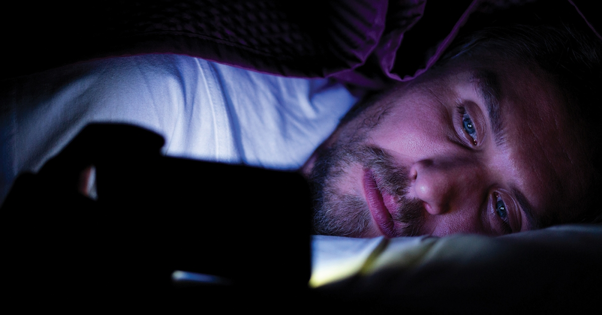 A person lying under the covers in a dark room and looking at a smartphone. (Cavan Images via Getty Images)