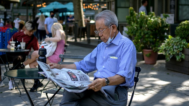 A man reads a newspaper in Bryant Park in New York City on May 19, 2021, as COVID-19 restrictions are lifted. (Ed Jones/AFP via Getty Images)