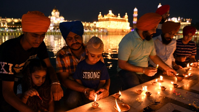 Sikh devotees light candles at the Golden Temple in Amritsar, India, on June 25, 2021. (Narinder Nanu/AFP via Getty Images)