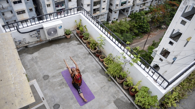 Yoga instructor Pratibha Agarwal practices yoga on a building's terrace in Hyderabad, India, in June 2020. (Noah Seelam/AFP via Getty Images)