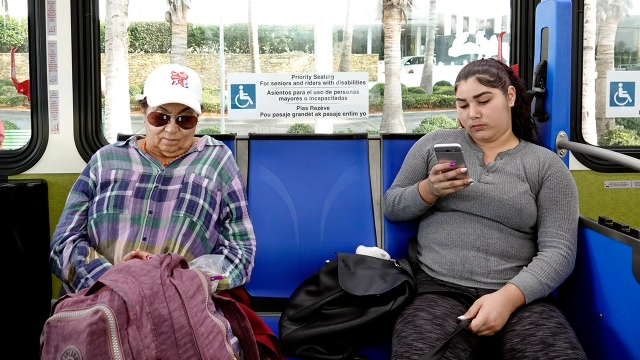 Passengers on a Florida bus look at their smartphones.