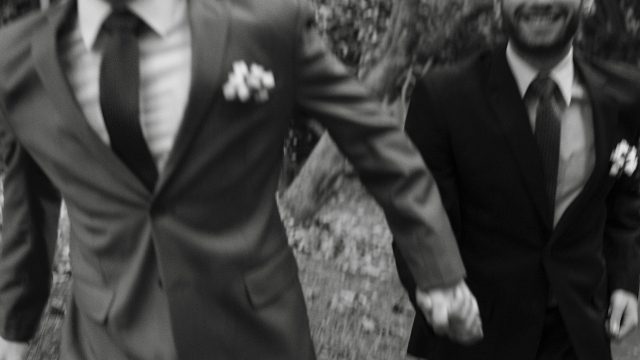 Two grooms hold hands while walking. (Unsplash/Maico Pereira)
