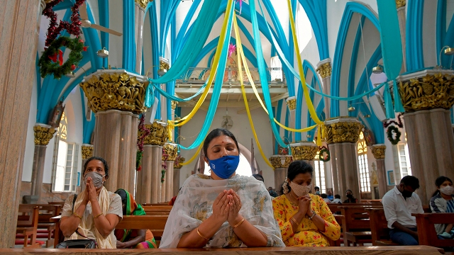 Christian devotees wearing face masks offer prayers at St. Mary's Basilica in Bengaluru on Dec. 24, 2020. (Manjunath Kiran/AFP via Getty Images)