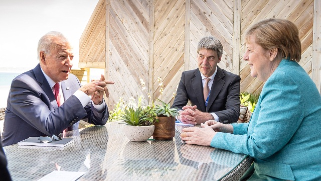 German Chancellor Angela Merkel and U.S. President Joe Biden meet at the sidelines of the G7 summit in Cornwall, England, together with Merkel's foreign policy adviser Jan Hecker on June 12, 2021.