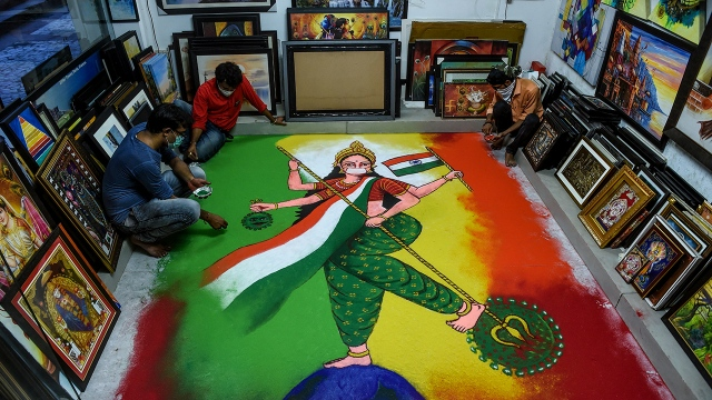 Artists create Hindu ritual artwork depicting India as a mother goddess holding the national flag and a symbol of the COVID-19 pandemic on the country's Independence Day on the outskirts of Ahmedabad on Aug. 15, 2020.