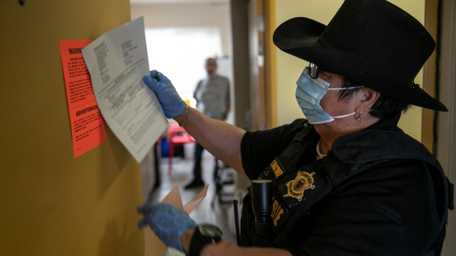 A Maricopa County constable posts an eviction order for nonpayment of rent in Phoenix on Oct. 1, 2020, despite a nationwide moratorium then in place on evictions from the Centers for Disease Control and Prevention during the coronavirus pandemic.