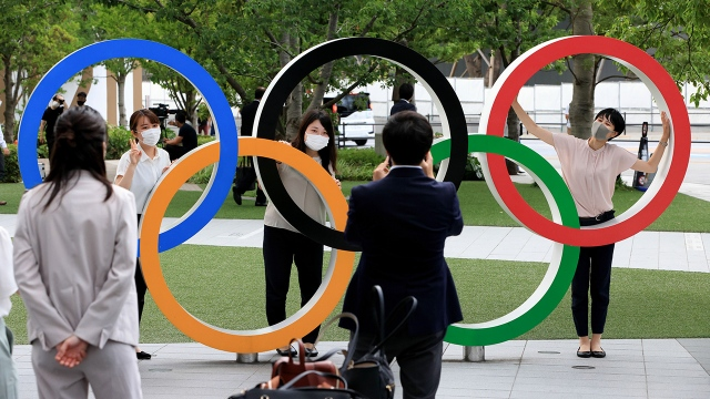 People wearing face masks take a photo in front of the Olympic Rings installation at the Olympic Square in Shinjuku, Japan.