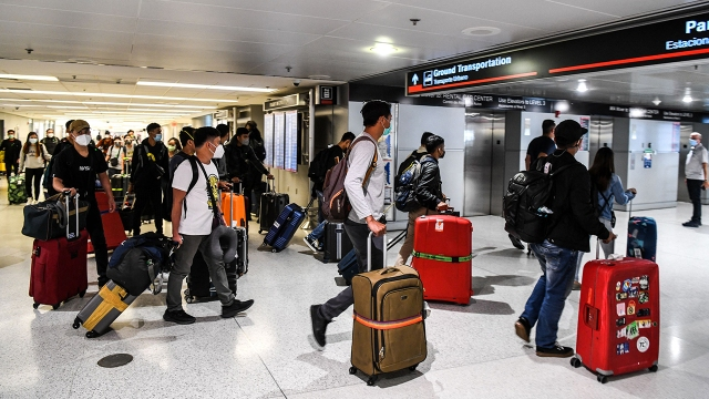 Travelers arrive at Miami International Airport ahead of Memorial Day weekend on May 26, 2021.