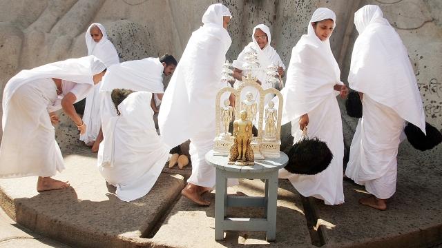 Jain nuns gather beneath the monolithic statue of Gommateshvara during the first day of the Mahamastakabhisheka ceremony on Feb. 8, 2006, in Shravanabelagola, India.