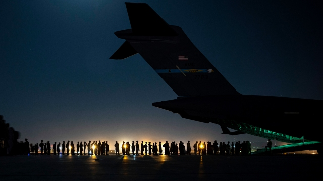 Evacuees line up to board a C-17 aircraft in support of the Afghanistan evacuation at Hamid Karzai International Airport on Aug. 21, 2021, in Kabul, Afghanistan.
