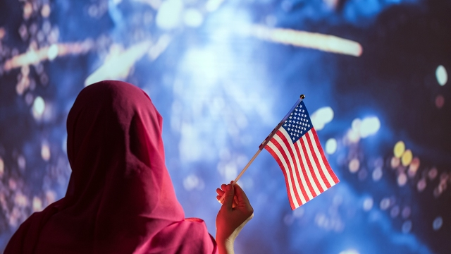 A Muslim woman in a headscarf holding an American flag during fireworks at night.