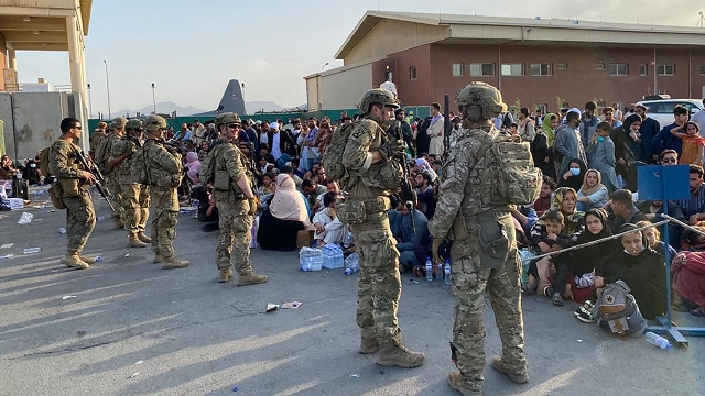 U.S. soldiers stand guard at the military airport in Kabul as Afghan people wait to board a military aircraft on Aug. 19 during the U.S. withdrawal from Afghanistan.