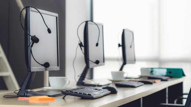 A series of computer monitors with headsets hanging on them.