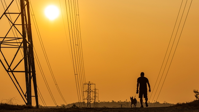Smoke-filled skies cast an orange hue at sunset as a man and his dog walk in Laguna Hills, California, on Sept. 16, 2020.