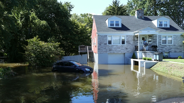 A car sits in a flooded driveway on Sept. 2, 2021, in Mamaroneck, New York, after Hurricane Ida passed through the region.