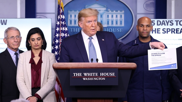Then-President Donald Trump, flanked by members of his coronavirus task force, speaks to reporters at the White House on March 16, 2020.