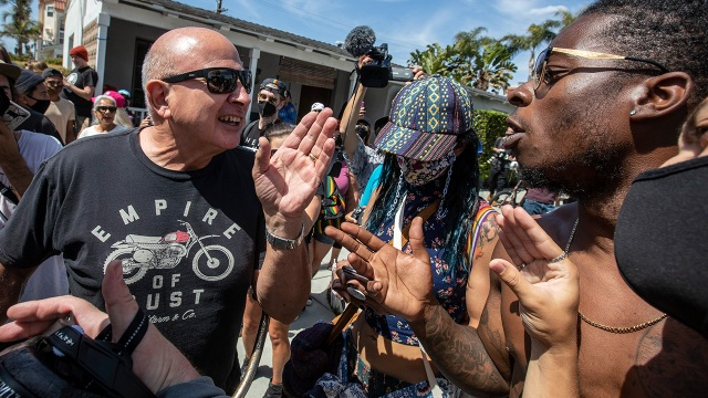 Two men argue as protesters demonstrate against a so-called White Lives Matter rally on April 11, 2021, in Huntington Beach, California.