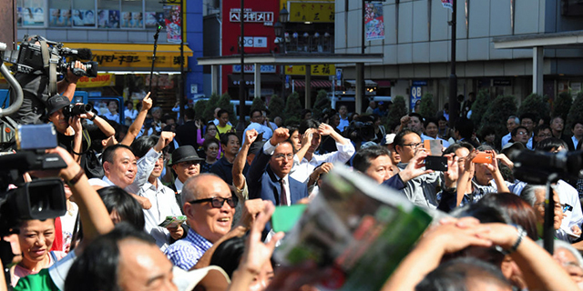 People listen to a street speech in Tokyo as the House of Representatives election campaign kicks off on Oct. 10. (The Asahi Shimbun via Getty Images)
