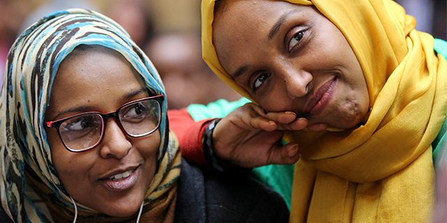 Shugri Elmi and Mariam Cheick listen to a speaker during Immigrants' Day at the Massachusetts State House in Boston on April 4. Both immigrated from Somalia and became citizens. (Craig F. Walker/The Boston Globe via Getty Images)
