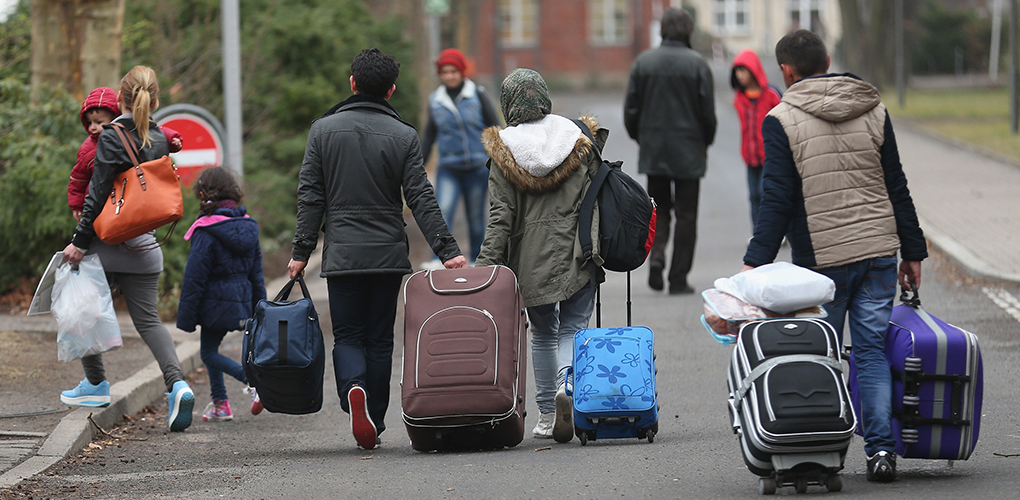 BERLIN, GERMANY - MARCH 11: People pulling suitcases arrive at the Central Registration Office for Asylum Seekers (Zentrale Aufnahmestelle fuer Fluechtlinge, or ZAA) of the State Office for Health and Social Services (Landesamt fuer Gesundheit und Soziales, or LAGeSo), which is the registration office for refugees and migrants arriving in Berlin who are seeking asylum in Germany, on March 11, 2015 in Berlin, Germany. Germany, which registered over 200,000 refugees in 2014, is expecting even more in 2015 and many cities and towns are reeling under the burden of having to accommodate them. The main countries of origin of the refugees include Syria, Serbia, Eritrea, Afghanistan, Iraq, Kosovo and Albania. (Photo by Sean Gallup/Getty Images)