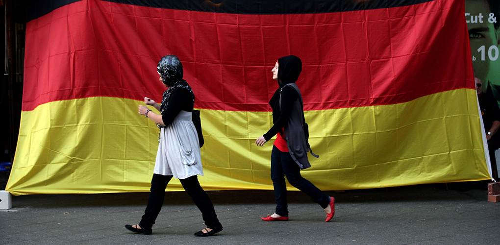 BERLIN - JULY 07: Two young Muslim women walk by a pub draped in a German flag in the Arab and Turkish-heavy neighborhood of Neukoellsn during the FIFA 2010 World Cup match between Germany and Spain on July 7, 2010 in Berlin, Germany. Many immigrants in Germany identify strongly with the German national team, in part because many of the team's members have African, Arab, Turkish or East European roots. (Photo by Sean Gallup/Getty Images)